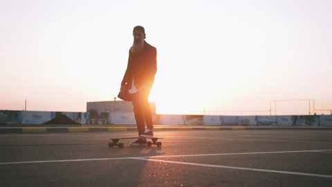 Stylish handsome middle-aged man with long gray beard standing with longboard during sunset on urban background