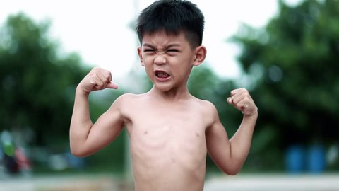 Little Asian boy shows his muscles outdoors . little boy winner sign outdoor