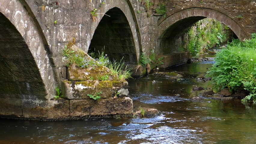 Old English architecture, arch stone bridge over river and tributary confluence or water flow junction