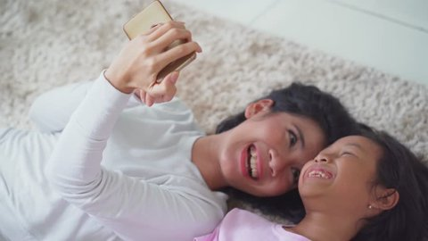 Happy young mother and her daughter lying on the carpet while looking at their photo on the mobile phone.