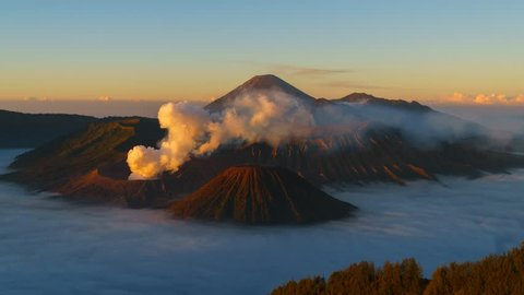 Timelapse of rolling cloud and smoke against mountain during sunrise in Bromo, Indonesia
