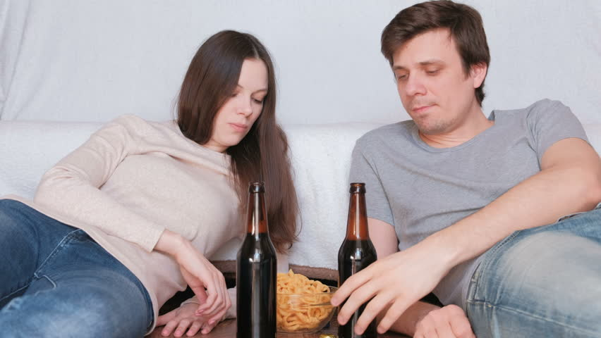 Couple young man and woman lie on the floor at home eating chips and drinking beer and talking.