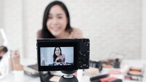 Young beautiful Asian woman professional beauty vlogger or blogger recording make up tutorial video with camera