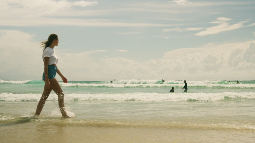 Beautiful girl walking across beach in Australia. Shot with a RED camera. 4k footage.