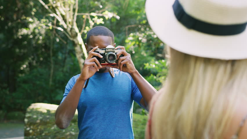 Handsome black guy taking pictures of beautiful blonde girl wearing a hat. Shot with a RED camera. 4k footage.