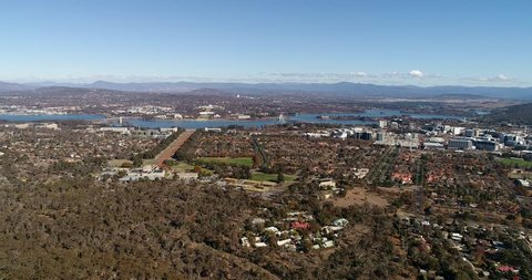 Canberra city suburbs around lake Burley Griffin on a sunny day – aerial panning in view of government district and city CBD towers.