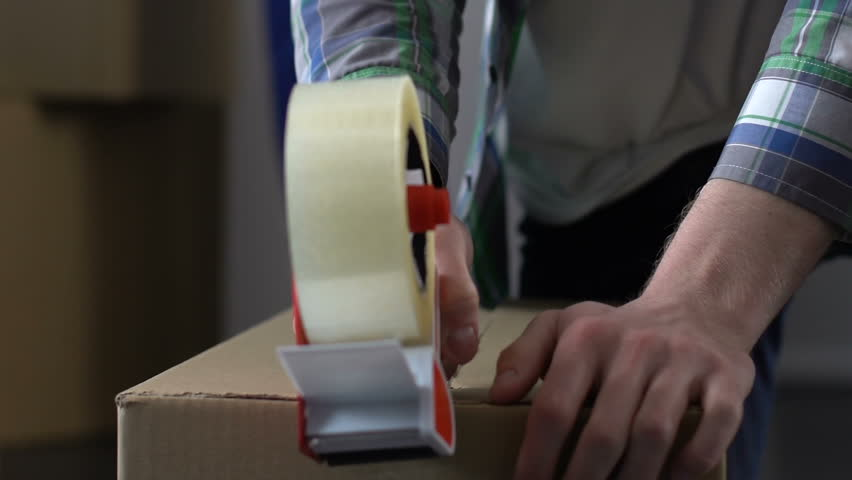 Man packing carton, relocation, moving service worker helping on background