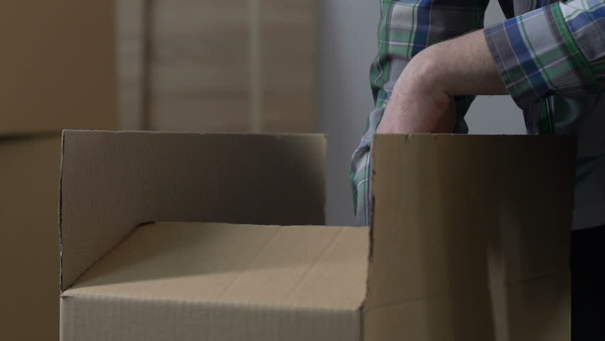 Man packing stuff into carton, divorce, division of property, moving from house