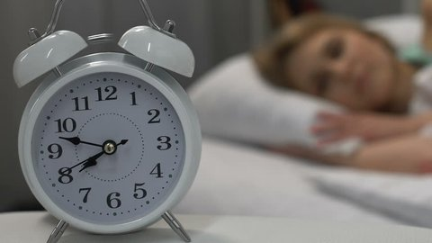 Alarm clock ringing and waking up blond woman lying in bed, morning time