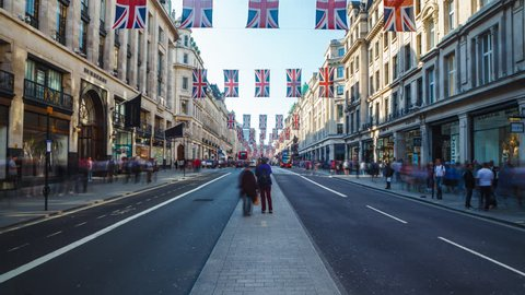 LONDON, UK - 19.05.2018: Traffic in London, Regent Street with pedestrians, Red Buses and black Cabs passing by. Daylight before sunset, street is full of British Flags.