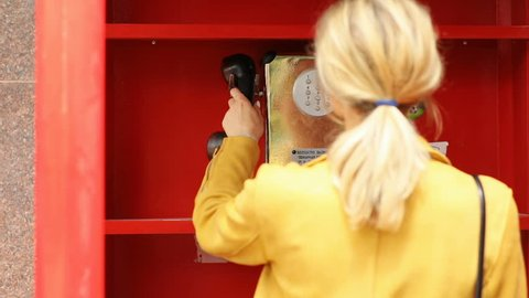 Portrait of young fashionable woman using public payphone for calling in red telephone booth call box girl speaking holding phone handset happy face expression communication concept worldwide connect