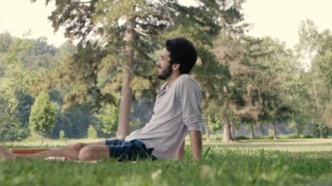 A Young Latino Man Rests in the Park Filming with an Old 16mm Film Camera on a Beautiful Summer Day. Old Tech in a Modern Usage Concept. Shot on the Canon C100, Cinematic Slow Motion