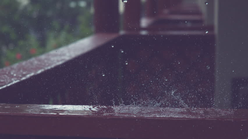 SLOW MOTION, CLOSE UP, DOF: Tiny raindrops fall on dark wooden railing and splash across porch. Monsoon rain washes the terrace of a lovely vacation house. Idyllic drops of water falling and splashing