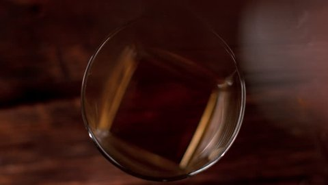 Super slow motion of falling ice cube into whiskey glass, top view. Filmed on cinema slow motion camera, 1000fps