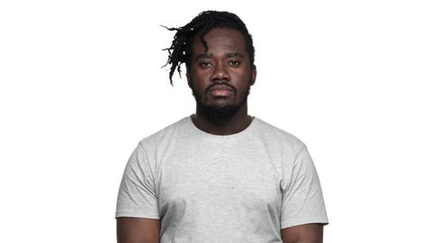 Portrait of uncaring african american man in casual t-shirt with afro pigtails throwing hands aside and shrugging don't know or can't help, isolated over white background. Concept of emotions