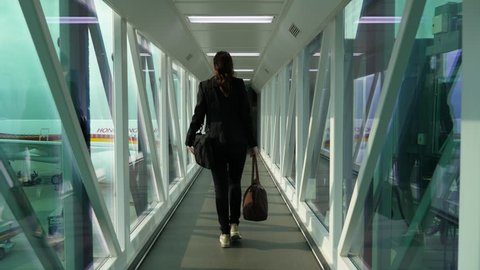 HONG KONG - MARCH 06, 2018: Professional woman arrived to international airport, walk at jet bridge to terminal building, slow follow camera. Business lady in formal wear carry laptop and handbag