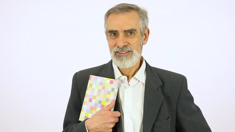 An elderly man holds a book, smiles at it and at the camera - white screen studio