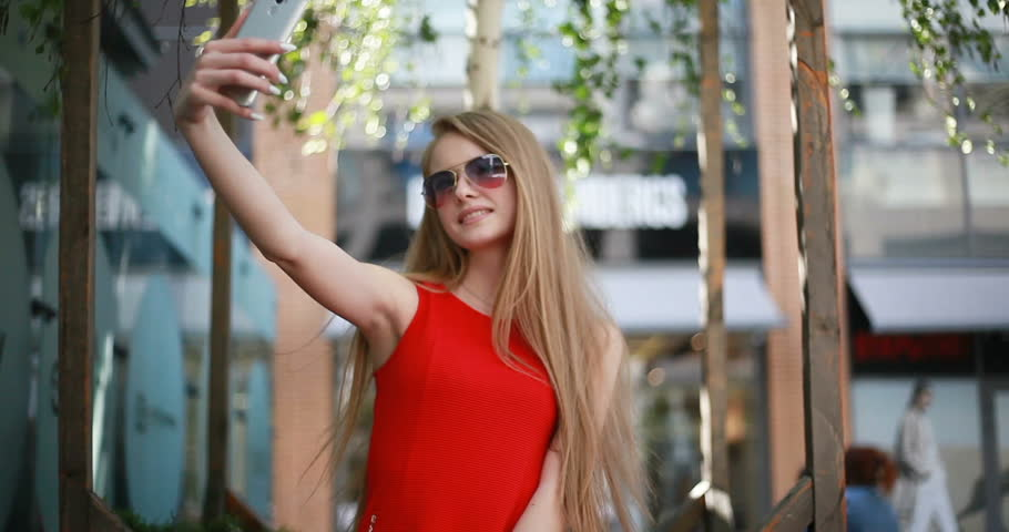 Selfie time, Young funky blogger is making photo for her social networks page. Young happy woman taking selfie on a nice summer day, dressed in a red dress. atmosphere and a beautiful smiling girl. | Shutterstock HD Video #1012312334