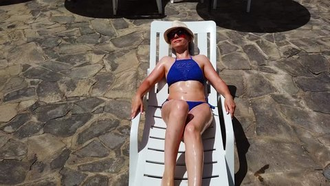 View from the top as a woman in a blue swimsuit sunbathes on a lounger, gets up, goes to the pool and swims in the pool
