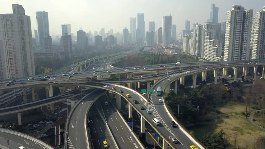 Shanghai China Road Junction traffic cars Elevated overpass complicated urban interchange Technology multilevel modern technological construction Skyscrapers cityscape fog day. Aerial Approach to 4k