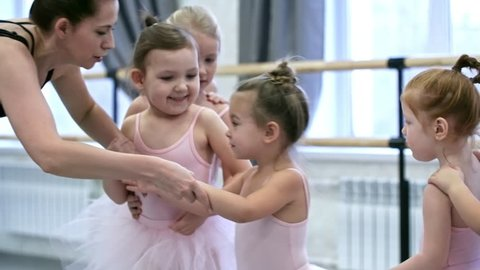 Medium shot of group of little girls in pink leotards and tutu skirts learning new dance moves during ballet lesson