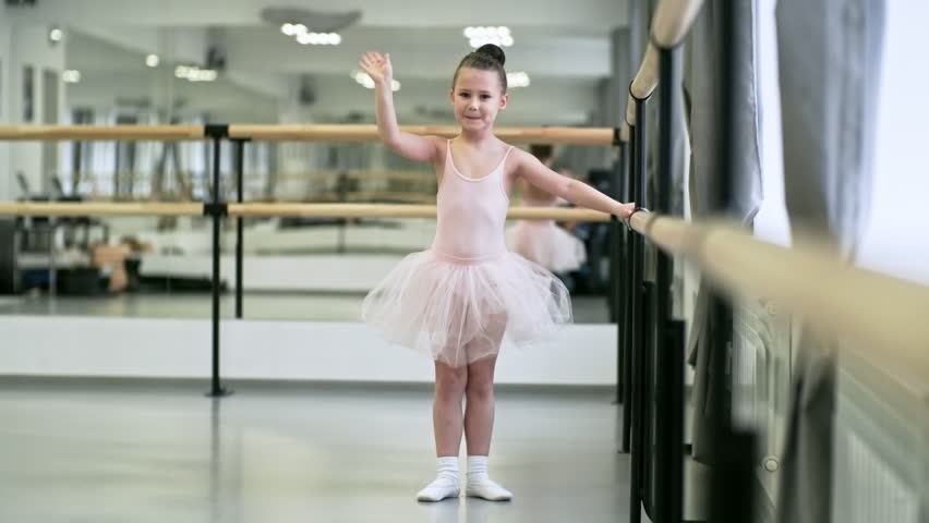 cf13e8bb987806 Portrait of little girl in light pink leotard and tutu skirt holding ballet  barre and waving hand to camera, tracking shot