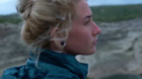 Young woman on coastline of Corsica with cliffs and crashing waves in slow motion