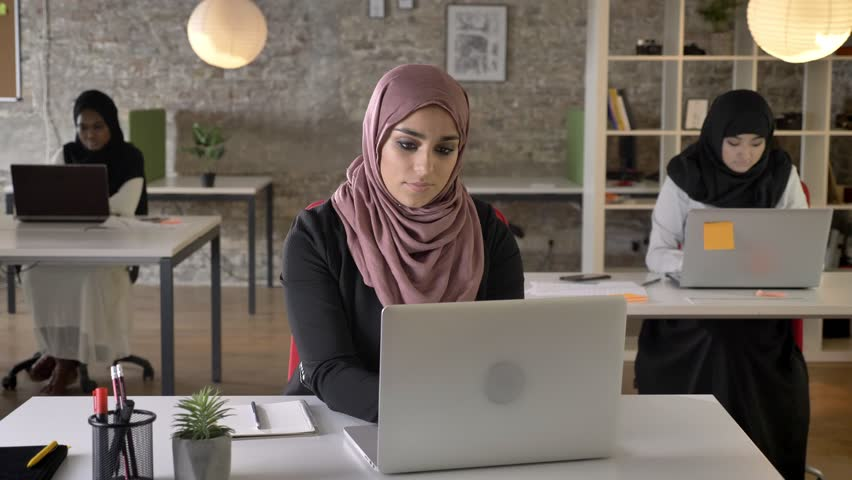 Three young muslim womans in hijab sitting and working in modern office, muslim beautiful woman looking in camera and smiling | Shutterstock HD Video #1012359404