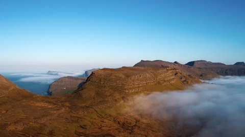 Aerial view on The Faroe (Føroyar) Islands (Denmark). High altitude. Flying with drone through clouds.