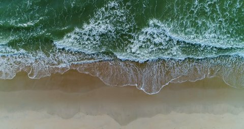 Beautiful 4K tropical beach aerial - a bird's eye view of ocean waves crashing against an empty beach from above