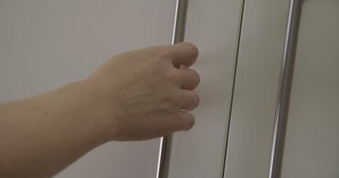 CU on woman's hand as she opens and closes white cupboard door in kitchen revealing white shelves and drawers. Locked off, real-time 4K