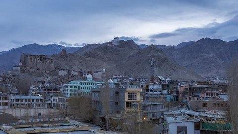 Aerial view of cityscape and high snow mountain range on rural desert landscape and Leh Palace with beautiful sunrise sky and amaizing cloud moving as background, viewed of rooftop Leh, Ladakh, India.