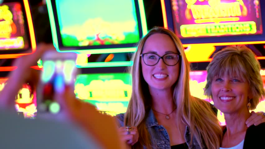 Man takes cell phone photo of mother and daughter in casino | Shutterstock HD Video #1012406024