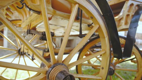 Retro carriage wooden wheel wrapped in iron close-up 4K. Dolly shot of wooden carriage wheel in focus of a parked retro renewed carriage in park.