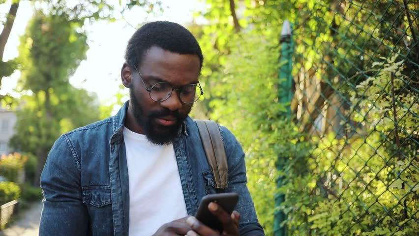Portrait african american young attractive man glasses using phone walk on street smile sunlight sunset cellphone computer fashion internet face outside technology businessmen black young city mobile #1012424924