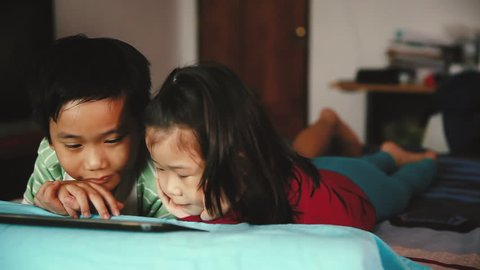 Pan video of asian children looking at digital tablet. Focus at chinese boy, younger sister lying prone on bed, near by. Conceptual about using E-learning technologies. Cinematic tone.