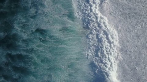 Big Waves rolling from above. Top down 4k drone view on blue turquoise ocean, breaking waves, whitewash. Sunny day over the sea. Huge swell hitting shoreline. Powerful waves Oahu, Hawaii North Shore