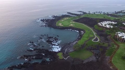 Golf course carved in lava rock. Green and black lava captured in aerial view from above. blue pacific ocean in evening light. palm trees around the green and small waves on rocky beach. Kona coast