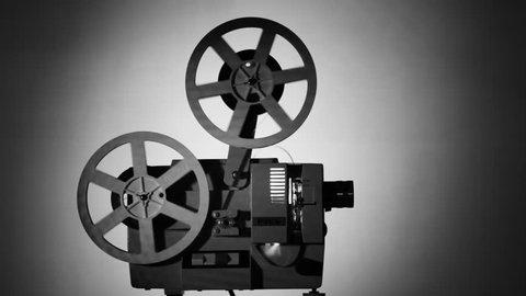 Movie projector 8-mm film. The film projector is loaded with a film and a film is shown. Monochrome image.