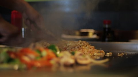 Chef preparing food on an open flat grill. Chopped vegetables and fried rice cooked at a restaurant. Close up of rice being fried by a Japanese chef.