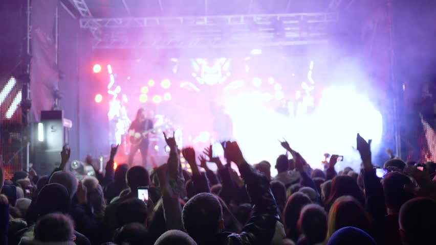 Kherson, Ukraine 30 March 2018: concert party, crowd of fans jumping into rhythm at rock festival with phones into hands in spotlight lighting in Kherson, 30 March 2018. #1012485464