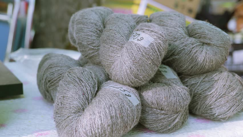 The gray thick rolled yarn on the white table displayed on the market on the stall | Shutterstock HD Video #1012496654