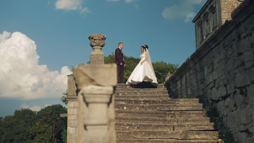 Lovely wedding couple standing together near old convergence | Shutterstock HD Video #1012519034