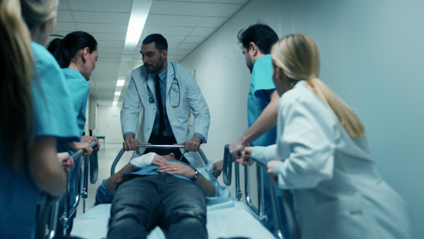 Emergency Department Doctors, Nurses and Surgeons Move Seriously Injured Patient Lying on a Gurney Through Hospital Corridors. Medical Staff in a Hurry Move Patient into Operating Theater. 4K UHD. | Shutterstock HD Video #1012593914