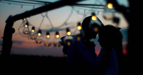 Sensitive portrait of two couple silhouettes standing behind the string of lights during the sunset. The guy is tenderly kissing the hands of the girl.