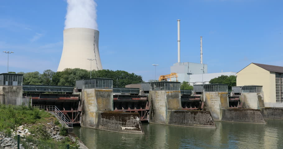 River dam with water power station in front of a nuclear power station with reactor house, funnel and huge, steaming cooling tower.