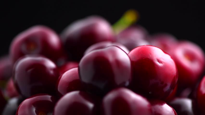 Fresh ripe Cherry close-up. Rotated Organic red cherries isolated on black background. Sweet Berries rotation. 4K UHD video
