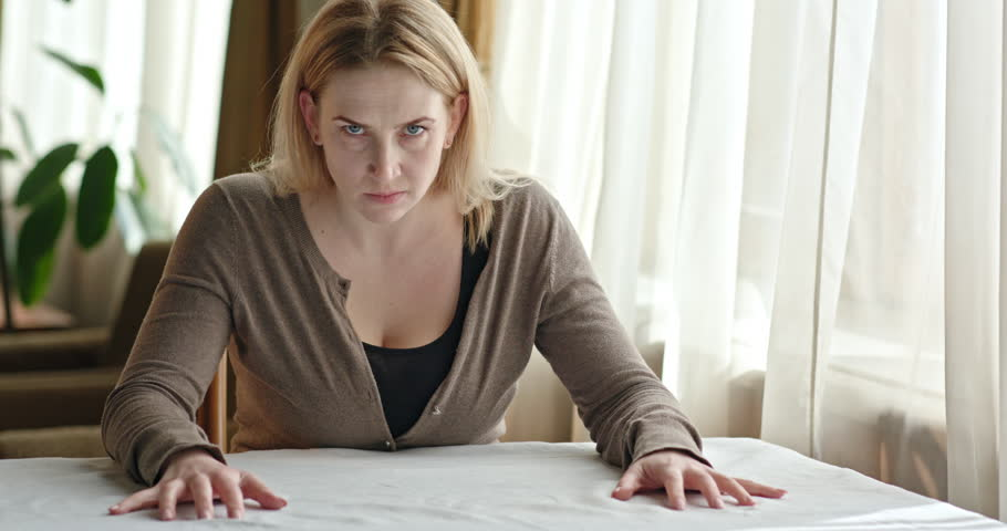 Nervous adult woman has a strong, angry look at the camera while sitting at the table in the room near the window