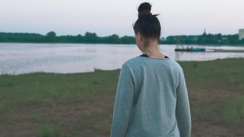 Young woman walking at coast in morning. Green grass, lake. Summer days. Slow motion. Healthy lifestyle concept | Shutterstock HD Video #1012647734