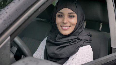 Young beautiful muslim girl in hijab is sitting in car in rainy weather, watching at camera, religiuos concept, transport concept
